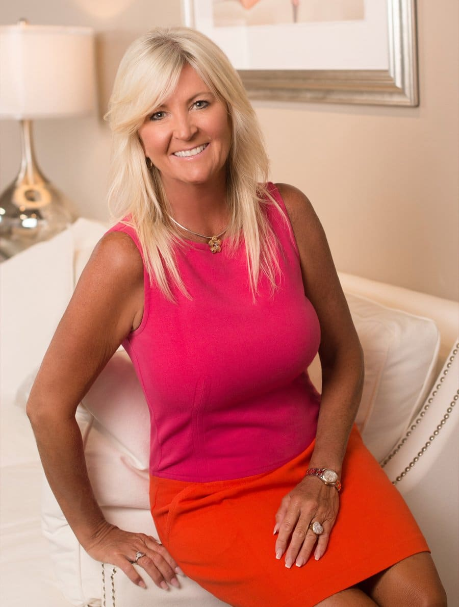 Golden Golf Services managing member Lisa Shirey sits on couch in pink and orange dress.