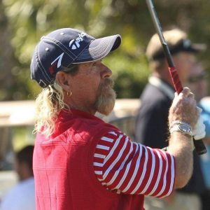 The late Walt Shirey plays golf in a red shirt with navy baseball cap.