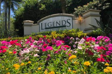 This planter bed of pink, red and yellow blooms sits in front of the Legends Golf Country Club sign wall.