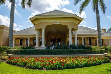 Exterior front view of a Southwest Florida clubhouse entrance that showcases a large planter bed of rich red begonia.